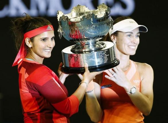 Switzerland's Martina Hingis (R) and India's Sania Mirza pose with the trophy after winning their doubles final match at the Australian Open tennis tournament at Melbourne Park, Australia, January 29, 2016.