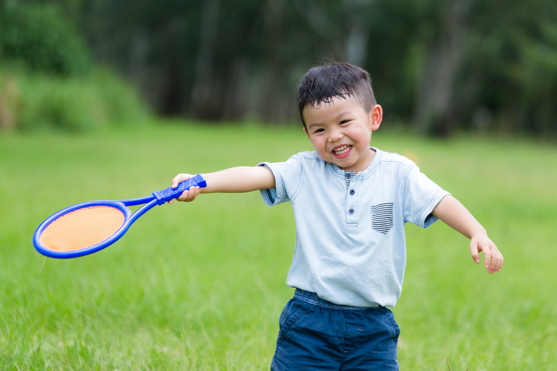 Thrilled little boy playing tennis at park