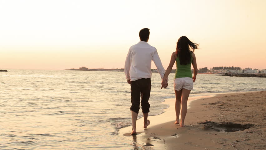 a couple holding hands and walking down the beach