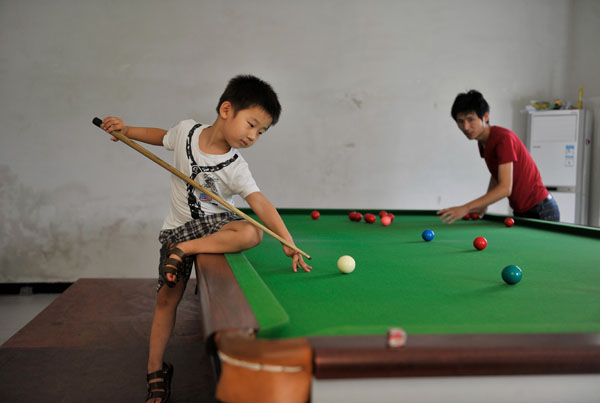 Three-year-old Wang Wuka practises snooker as his father positions the balls on the table at their home in Xuancheng