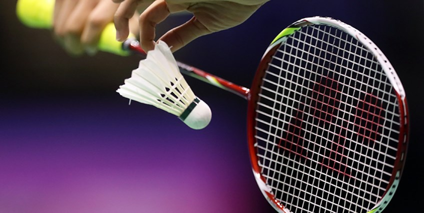 A player holding a racket and shuttlecock